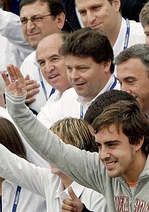Alonso saluda en el circuito Ricardo Tormo rodeado por los asistentes a las clases de conducción segura. (Foto: EFE)