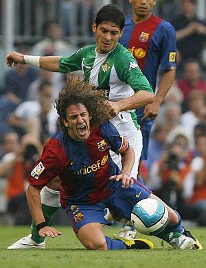 Puyol protege la pelota ante Edu. (Foto: EFE)