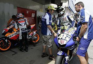 Rossi (d) y Pedrosa se bajan de sus motos tras terminar los entrenamientos. (Foto: AFP)