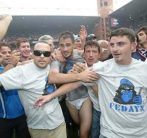 El defensa del Nápoles Paolo Cannavaro, hermano del madridista Fabio, es rodeado por aficionados nada más sellar el ascenso. (Foto: EFE)