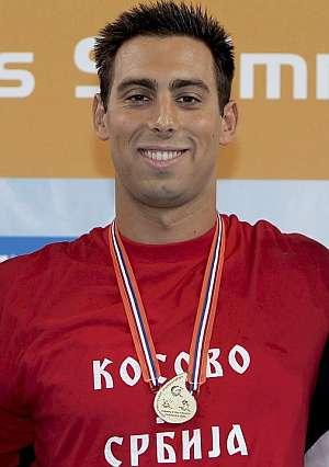 Cavic, en el podio con su medalla y la polémica camiseta. (Foto: AFP)