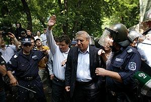 Un policía protege al presidente del CSKA, Alexandar Tomov, durante unas protestas por la situación del equipo (Foto: REUTERS)