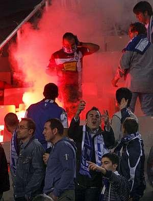 Aficionados del Espanyol junto a la bengala lanzada por los hinchas del Barcelona. (Foto: EFE)