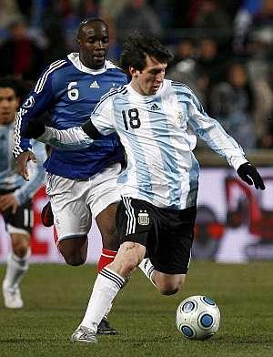 Leo Messi disputa un balón con Lass Diarra. (Foto: EFE)