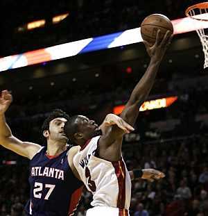 Pachulia intenta frenar a Wade. (Foto: AP)
