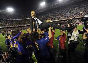 Guardiola, manteado por sus jugadores. (EFE)