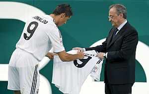 Cristiano Ronaldo firma una camiseta, en presencia de Florentino Pérez. (EFE)