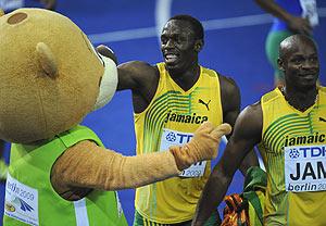 Bolt (c) y Powell, junto a Berlino, tras la final del 4x100. (Foto: AFP)
