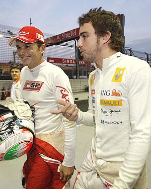 Fernando Alonso dialoga con Giancarlo Fisichella en el paddock de Singapur. (Foto: AP)
