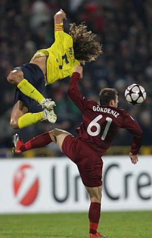 Carles Puyol pelea un balón aéreo contra Gokdeniz Karadeniz. (AP)