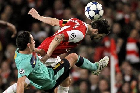 Xavi y Cesc disputan una jugada en el estadio Emirates. | Efe