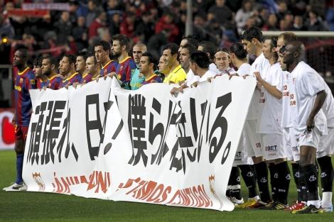 Los jugadores del Sevilla y del Barcelona sostienen una pancarta de apoyo (Foto: EFE).