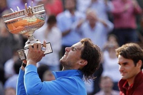 Nadal levanta la Copa de los Mosqueteros con Federer al fondo. | Ap