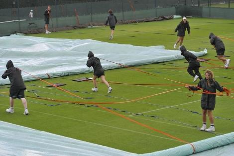 Varios operarios cubren con lonas un pista en Wimbledon. (Foto: Reuters)