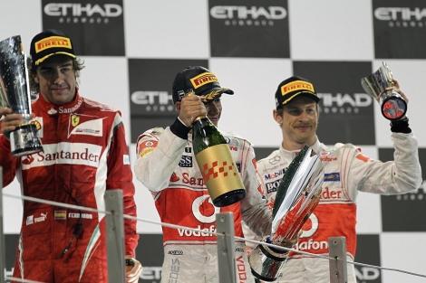 El piloto de Ferrari en el podio de Abu Dabi, juto a Hamilton y Button.   EFE