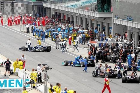 Los mecánicos retiran los coches en el Gran premio de Indianápolis.   REUTERS