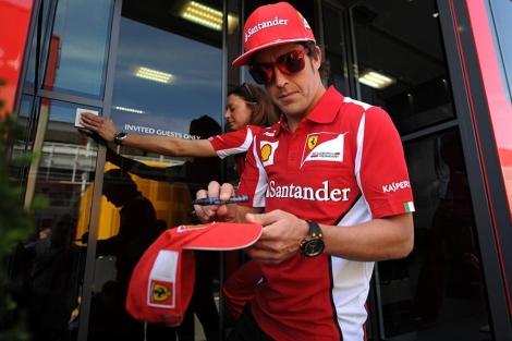 Alonso firma un autógrafo en el 'paddock' de Montmeló. (Foto: Afp)