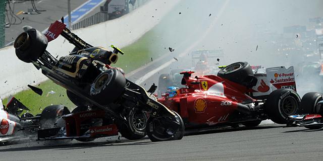 Fernando Alonso recibe el impacto de Romain Grosjean. | AFP