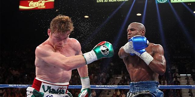 Mayweather golpea a 'Canelo' Álvarez, durante el combate.   Afp