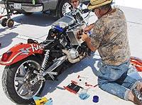 Un participante da los últimos retoques a su moto.