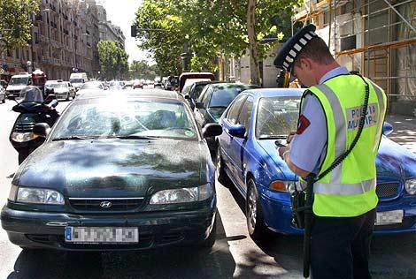 Un policia municipal multa a los coches estacionados en doble fila en Madrid.   D. S.
