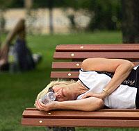 Una mujer duerme la siesta en el Retiro (Foto de archivo | AFP)