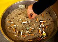 Un fumador apaga su cigarrillo antes de entrar en el metro. (Foto: Sergio Perez | Reuters)