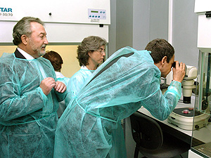 Zapatero observa en un microscopio una de las líneas celulares del Cabimer, que dirige Bernat Soria, a la izquierda. (Foto: EFE)