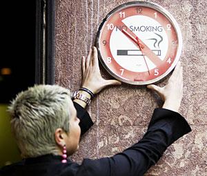 Una mujer coloca un reloj que prohíbe fumar. (Foto: EFE | Luis Tejido)