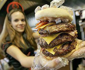 Una camarera muestra una hamburguesa triple (Foto: AP | Matt York)