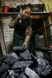 Una mujer rompe carbón para hacer un fuego.