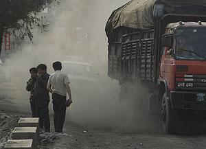 Varias personas se cubren ante el paso de un camión en China. (Foto: Reuters)
