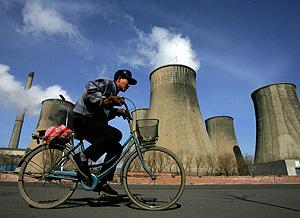 Un hombre pedalea junto a una central eléctrica en China (Foto: AP | Greg Baker)