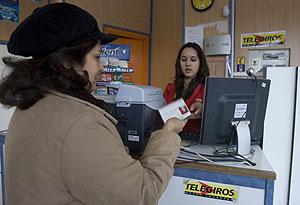 Una mujer inmigrante entrega un giro postal. (Foto: Iñaki Andrés)