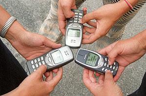 Tres jóvenes envían mensajes con sus móviles. (Foto: Diego Sinova)
