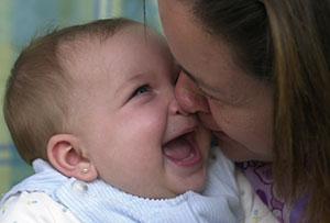 Una niña sonríe ante los arrumacos de su madre. (Foto: Carlos García)