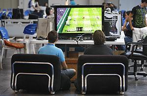 Dos jóvenes participan en una partida de fútbol de un videojuego. (Foto: Benito Pajares)