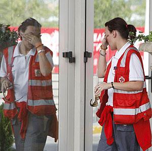 Una voluntaria de Cruz Roja enjuga su rostro a las puertas del hotel Auditorium. (Foto: EFE)