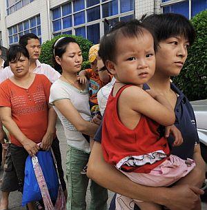 Varios padres chinos acuden con sus hijos a una revisión por el caso. (Foto: REUTERS)
