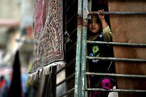 Una niña refugiada palestina mira a través de una improvisada valla en el campo de refugiados de Al Shatea. (Foto: EFE)