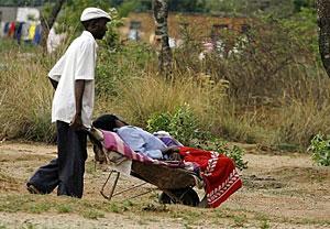 Un hombre lleva a un pariente enfermo de cólera al hospital en una improvisada camilla. (Foto: AFP)