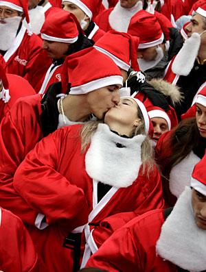 Unos jóvenes disfrazados de Papa Noel se besan en Bucarest, Rumanía. (Foto: Robert Ghement | EFE)