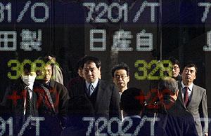 Varias personas se reflejan en el panel de un centro financiero en Tokio. (Foto: Reuters)