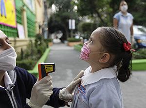 Un profesor toma la temperatura en el primer día de vuelta a clase en México (Foto: AP | Gregory Bull)