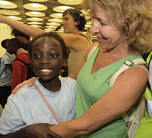 Ana de Pablos recibe a una niña de acogida en el aeropuerto (Foto: Infancia Solidaria)