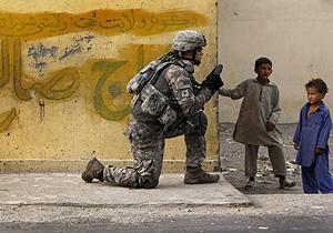 Dos niños observan a un soldado americano en Afganistán (Foto: Reuters | Tim Wimborne)