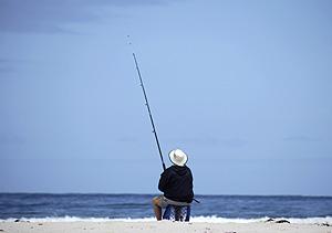 Un hombre pesca en la playa (Foto: Reuters | Kai Pfaffenbach)