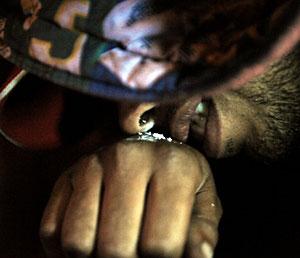 Un miembro de una banda esnifa cocaína en Medellín, Colombia. (Foto: Raul Arboleda | AFP)