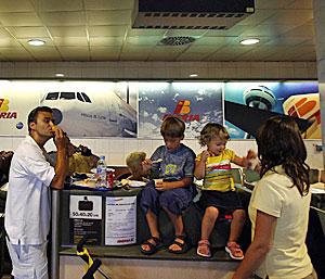 Varios niños esperan en un mostrador del aeropuerto (Foto: Santi Cogolludo)