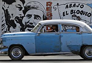 Un coche circula frente a un mural por las calles de la Habana (Foto: Desmond Boylan)